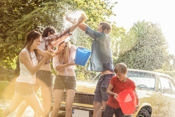 Group of friends washing yellow vintage car in summer having fun