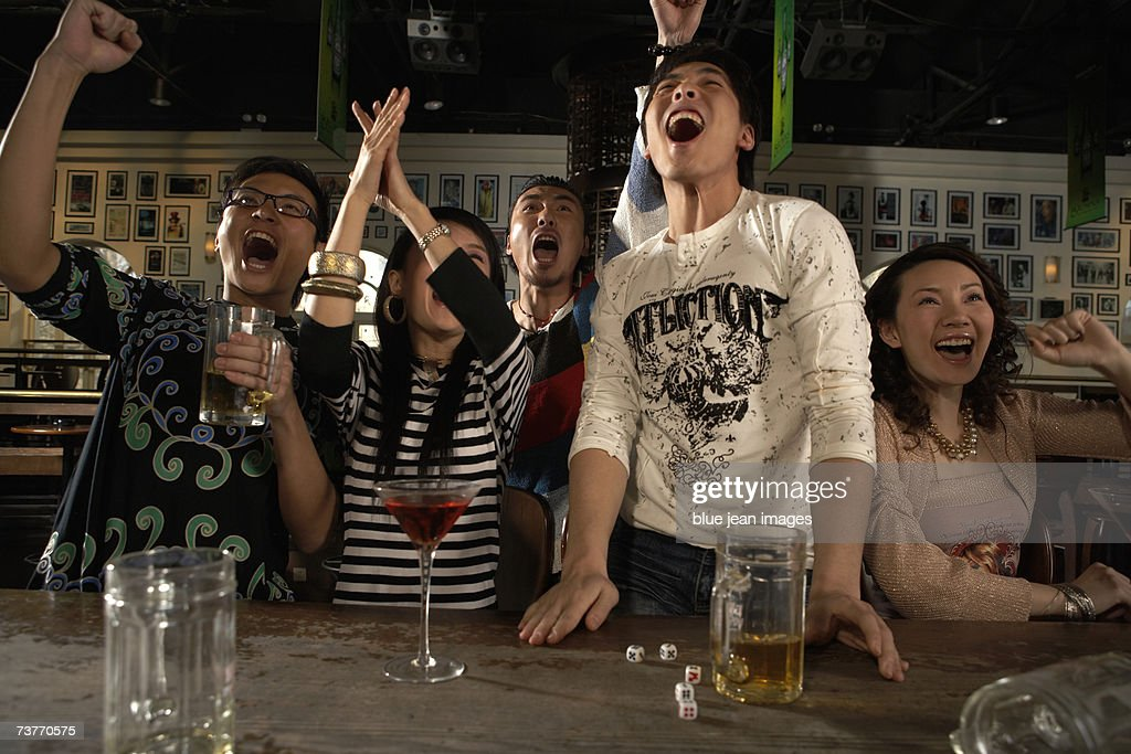 A group of friends watches a sporting event with drinks at a sports bar : Stock Photo