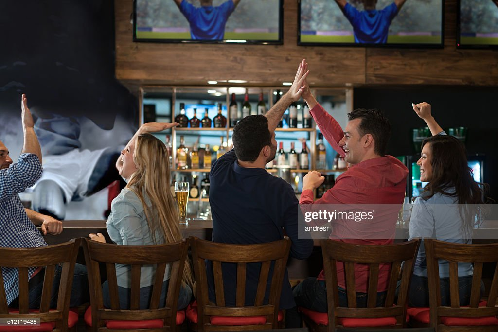 Group of friends watching a football game at the pub : Stock Photo