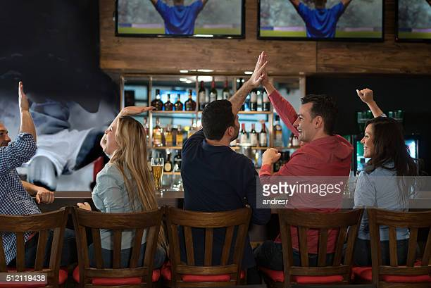 group of friends watching a football game at the pub - american football sport stockfoto's en -beelden