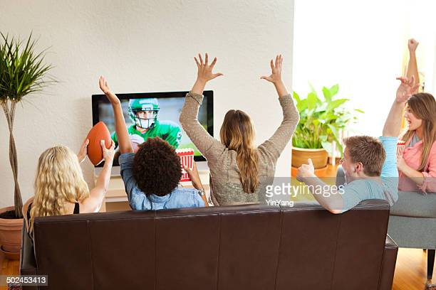 group of friends watching and cheering football game together - family watching tv stock pictures, royalty-free photos & images