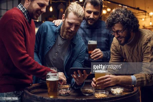 gruppe von freunden, die fußball auf dem smartphone beobachten und gemeinsam bier trinken - club football stock-fotos und bilder