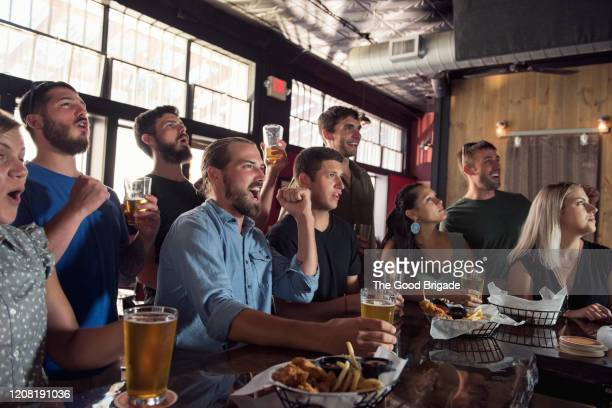 group of friends watching game in bar - sport stock pictures, royalty-free photos & images