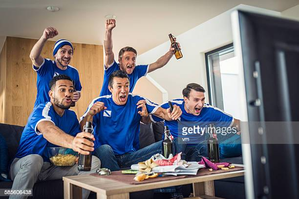 Group of friends watching game on TV