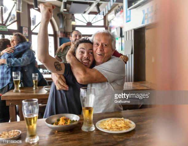gruppe von freunden beobachten fußballspiel in bar feiern ziel - punkten stock-fotos und bilder