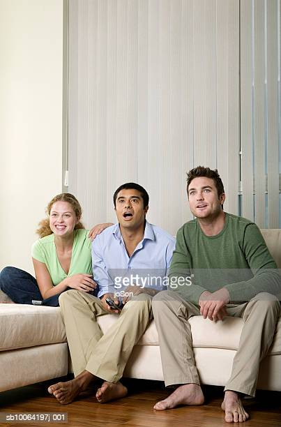 Group of friends watching television, smiling
