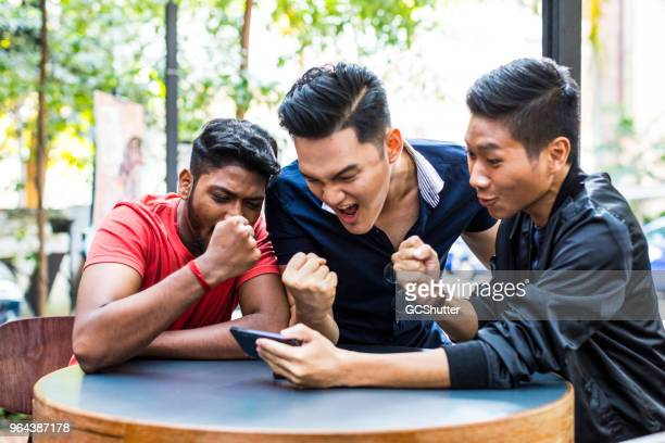 group of friends watching their favorite match on a mobile phone - match sportivo foto e immagini stock