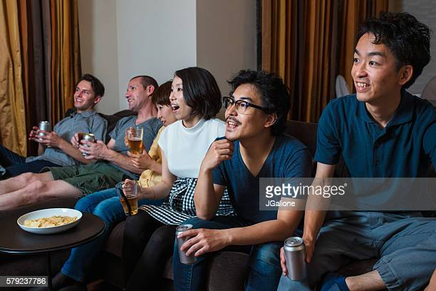 group of friends watching tv together - jgalione stock pictures, royalty-free photos & images