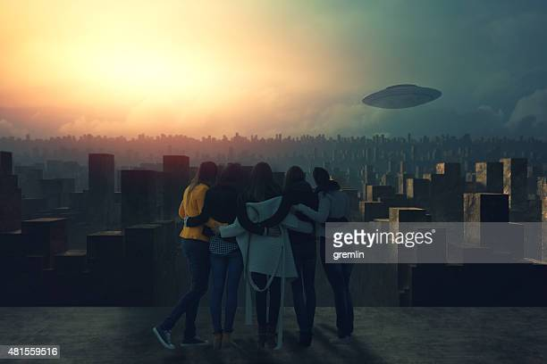 Group of friends watching UFO over the city