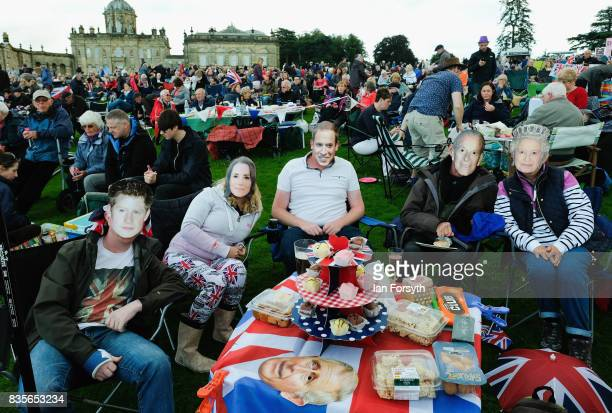 A group of friends wear British Royal family face masks as they attend the annual Castle Howard Proms Spectacular concert held on the grounds of the...