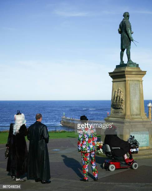 Group of friends wearing goth clothing stand next to the Captain Cook monument during the Whitby Goth Weekend on October 27, 2017 in Whitby, England....
