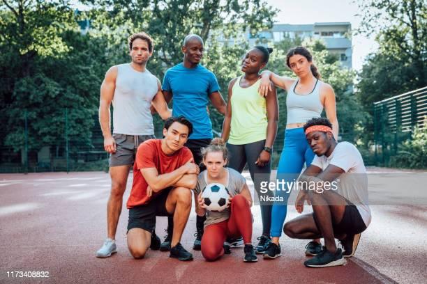 gruppe von freunden mit einem fußball - person gemischter abstammung stock-fotos und bilder