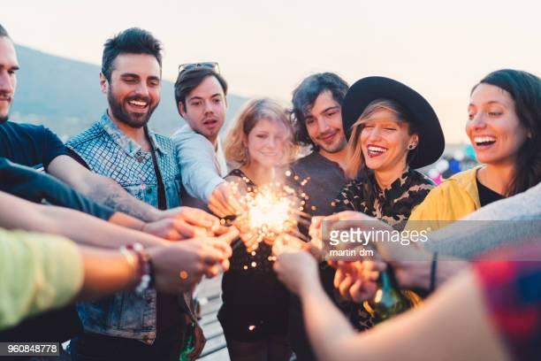 Gruppe von Freunden mit brennenden Wunderkerzen auf Party auf dem Dach