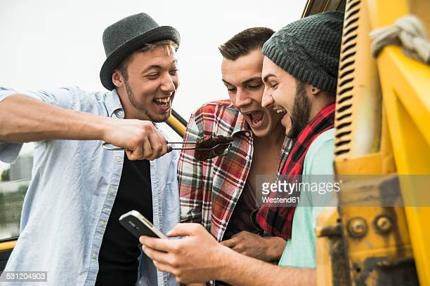 Group of friends with cell phone and steak at a car