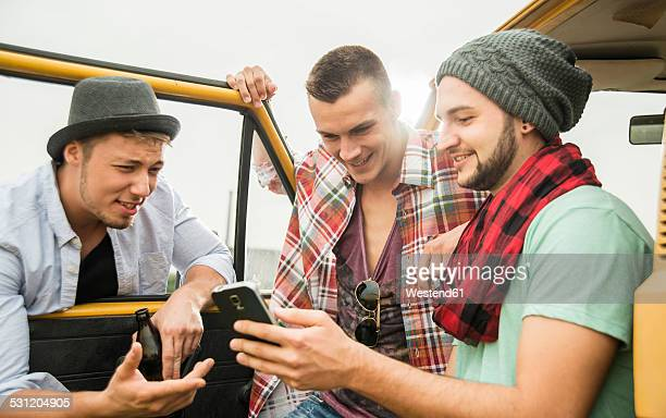 Group of friends with cell phone at a car