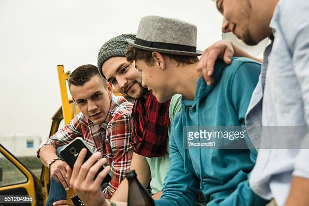 Group of friends with cell phone on pick-up truck
