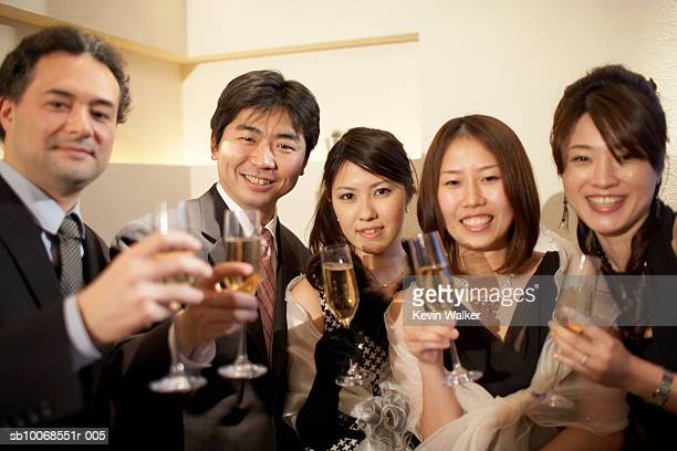 Group of friends with champagne flute at party, smiling