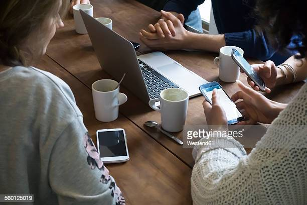 Group of friends with laptop using smartphones in a cafeteria