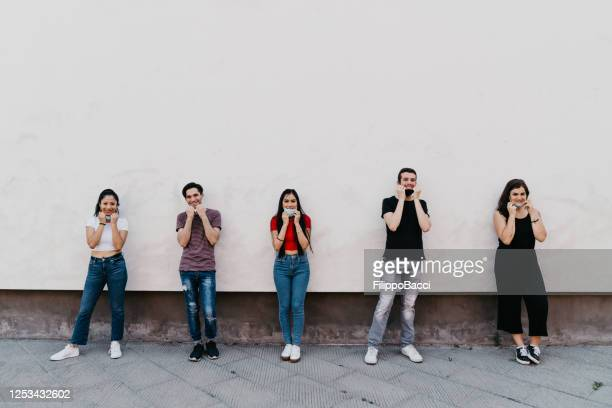 group of friends with protective face masks against a wall in the city - five people stock pictures, royalty-free photos & images