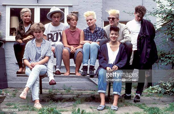 A group of friends with punk haircuts sitting on a bench in a back garden UK 1980's