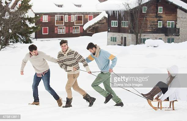Group of friends with sledge in the snow