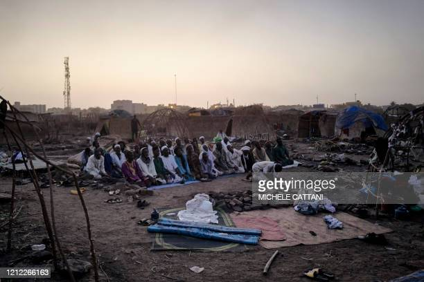 TOPSHOT A group of Fulani displaced people gather for the evening prayer between the ruins left by the fire that ravaged the camp a week earlier in...