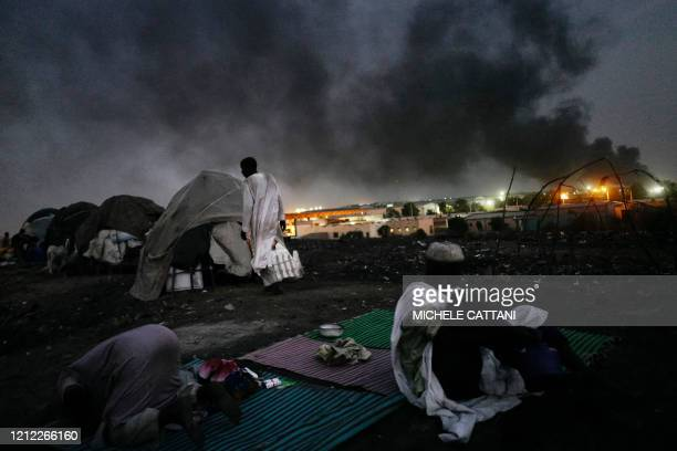 TOPSHOT A group of Fulani displaced people gather for the evening prayer while on the background someone burns tires in Bamako on May 7 2020 A week...