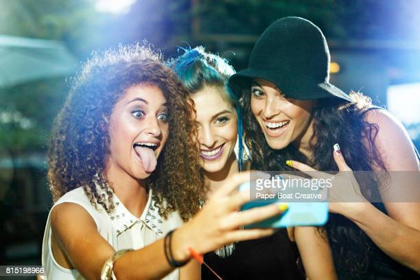 Group of funky teen friends taking a selfie with funny faces
