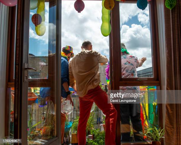 group of gay men celebrating gay pride at home on their balcony. - individual event stock pictures, royalty-free photos & images
