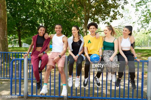 group of gen z friends sitting on a fence - medium group of people stock pictures, royalty-free photos & images