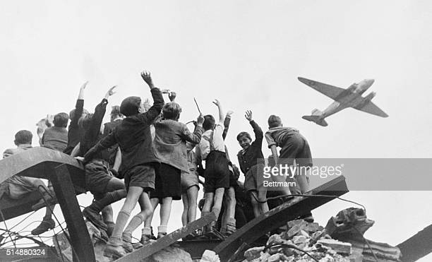 Group of German children stand atop building rubble, cheering a United States cargo airplane as it flies over a western section of Berlin. American...