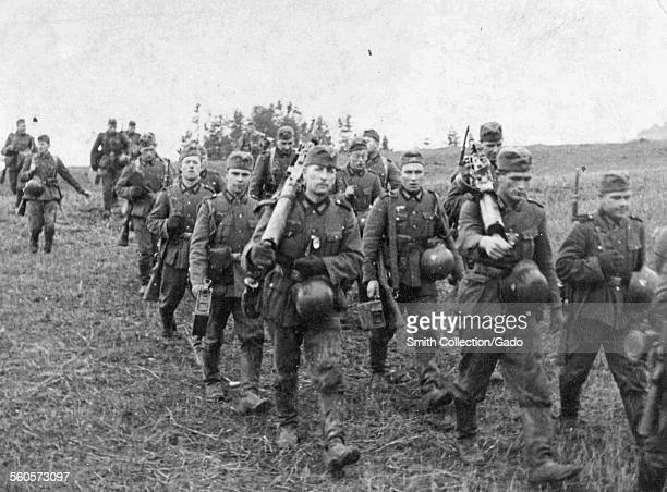 Group of German Nazi soldiers wearing uniform and carrying weapons marching through a field Germany 1942