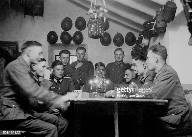 A group of German officers have a Christmas celebration with food and drink in the barracks