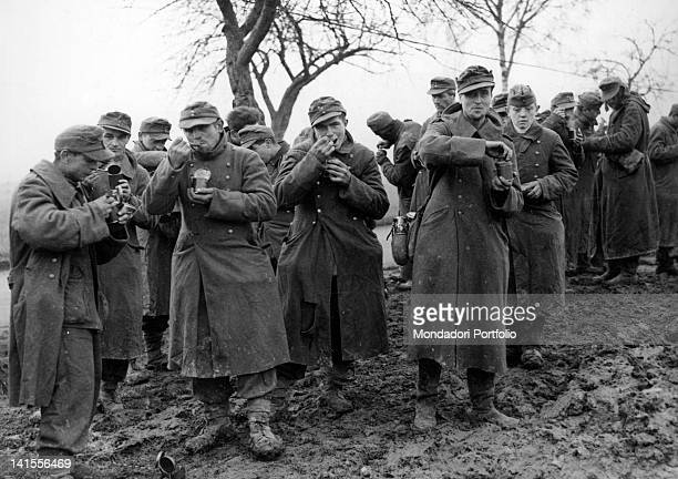 A group of German soldiers captured in Alsace and prisoners of the Allied Seventh Army eating canned food Alsace November 1944