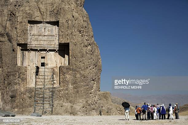 Group of German tourists visit the tomb of Achaemenid empeor, Darius I the Great at Naqsh-e Rostam necropolis, located about 12 km northwest of...