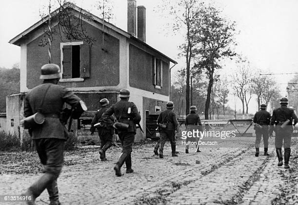 A group of German troops advance past a barricade in a small village during the invasion of France
