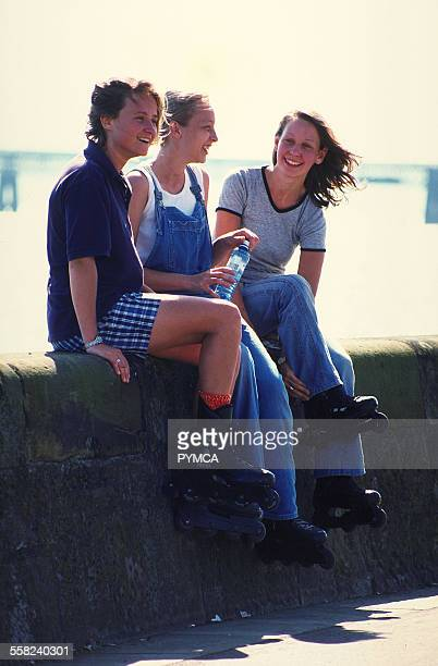 Group of girl rollerbladers sitting on a wall