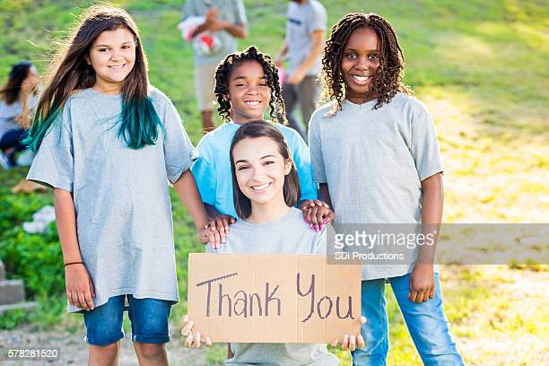 Group of girl volunteers holding up a 'Thank You' sign