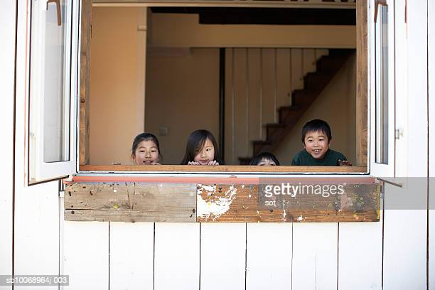 Group of girls and boy (4-13) hiding by the window,