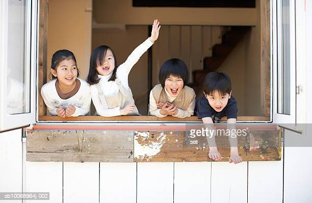 Group of girls and boy (4-13) smiling by window