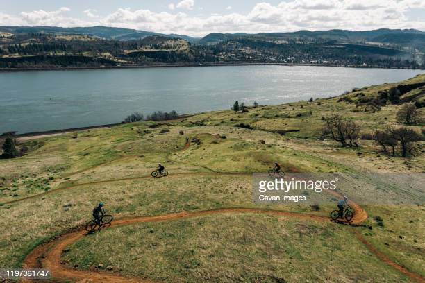 a group of girls bike along a trail overlooking the columbia river. - columbia river gorge stock pictures, royalty-free photos & images