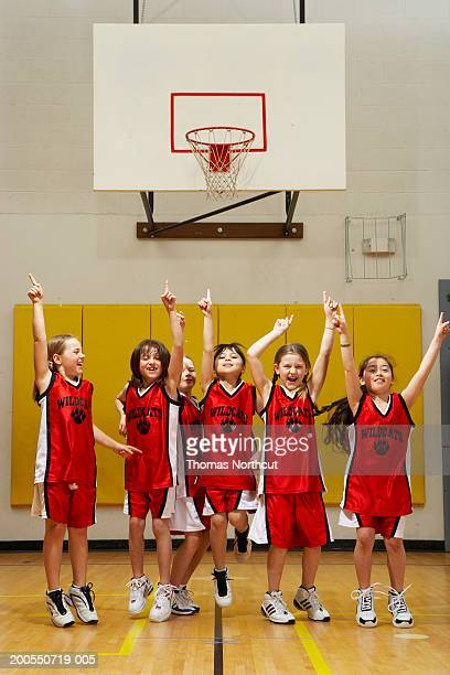 Group of girls (8-10) cheering on basketball court, arms raised