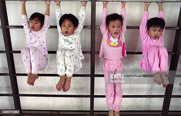 A group of girls do knee bends at the Li Xiaoshuang Gymnastics School in Xiantao China Li Xiaoshuang was a sucessful Chinese gymnast who was born in...