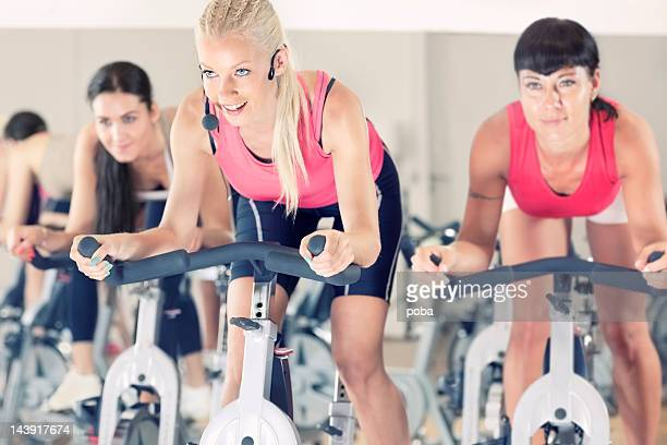 group of  girls spinning on bicycles in  gym.