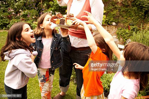 Group of girls (7-9) gathered around woman holding cake, outdoors