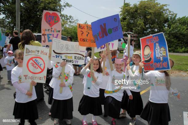 A group of girls holding posters at the Lag B'omer Jewish Unity Parade and Fair