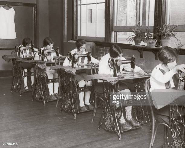 A group of girls in a sewing class at an American high school circa 1930
