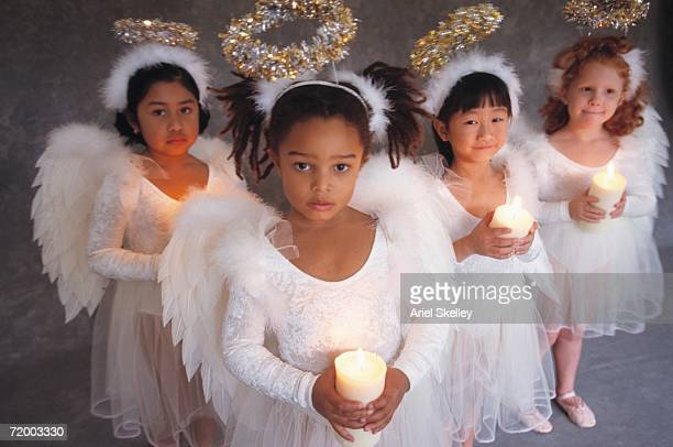 Group of girls in angel costumes holding candles