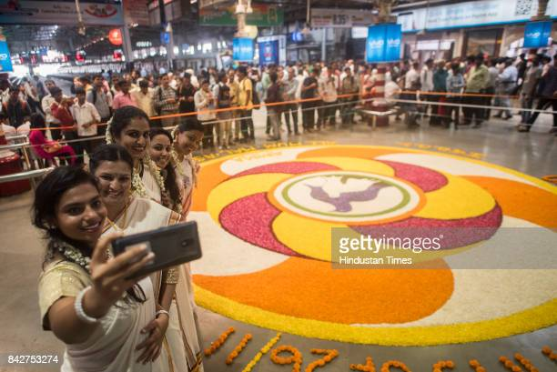 A group of girls in traditional saree take selfie in front of a huge rangoli made by flower petals on the occasion of Onam at CST Station on...