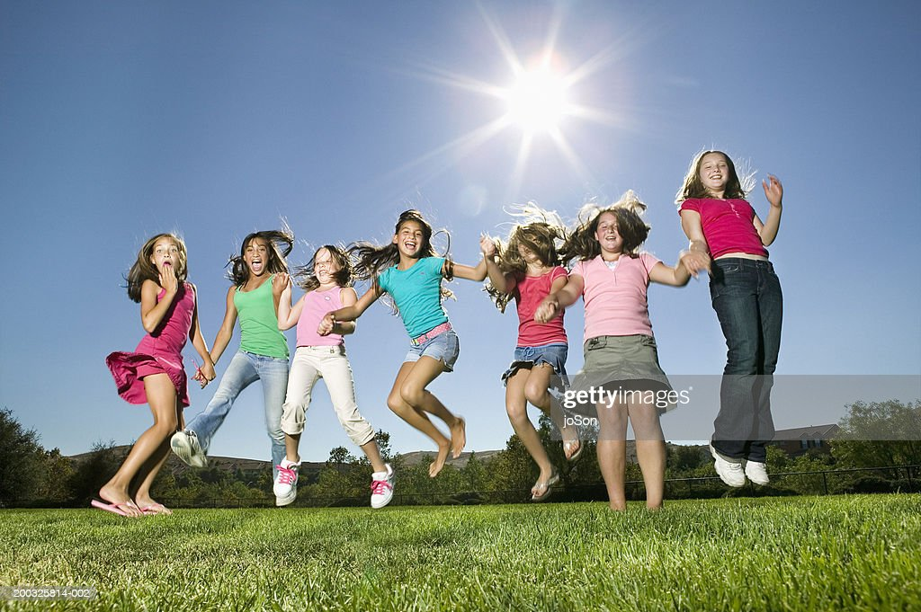 group of girls jumping up and down laughing ストックフォト getty